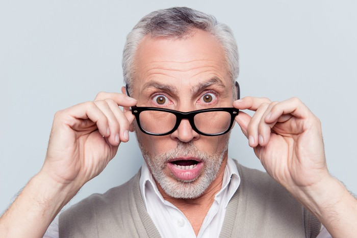 An older man looks shocked as he takes off his glasses for a closer look.