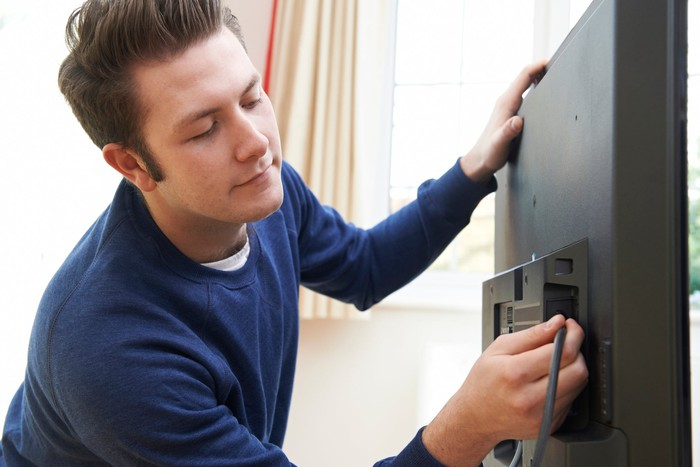 A young man plugs a coaxial cable into the back of a television.