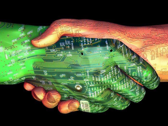 Close-up rendering of two hands performing a handshake. One hand is fair-skinned and the other one is green, and both are covered in circuit board-like patterns.