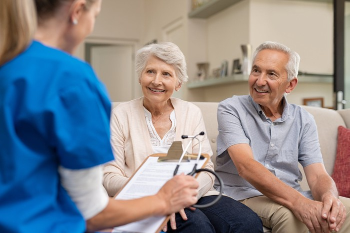 Elderly couple sitting on couch together, speaking with a healthcare provider wearing blue scrubs and holding a clipboard with paper on it