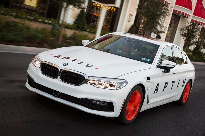 A white BMW sedan with Aptiv logos and visible self-driving sensor hardware