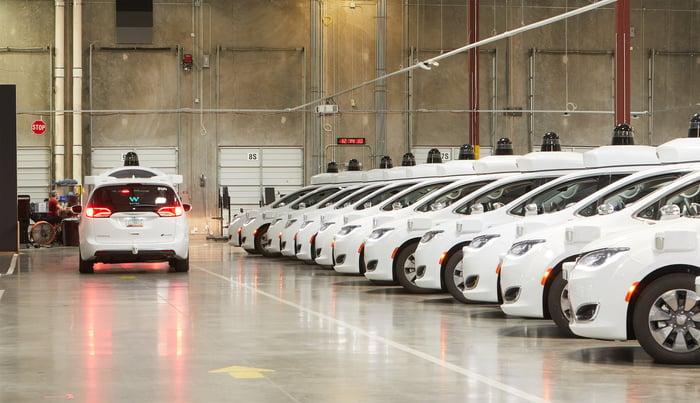 A line of Waymo's autonomous vehicles inside a building.