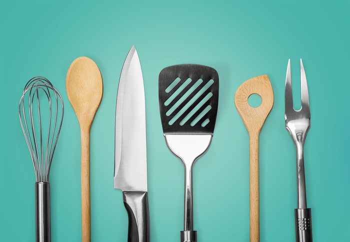 An array of kitchen utensils including a knife, whisk, and spatula on a blue background