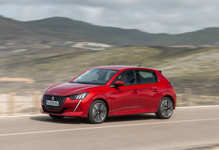 A red 2020 Peugeot 208, a small four-door hatchback.