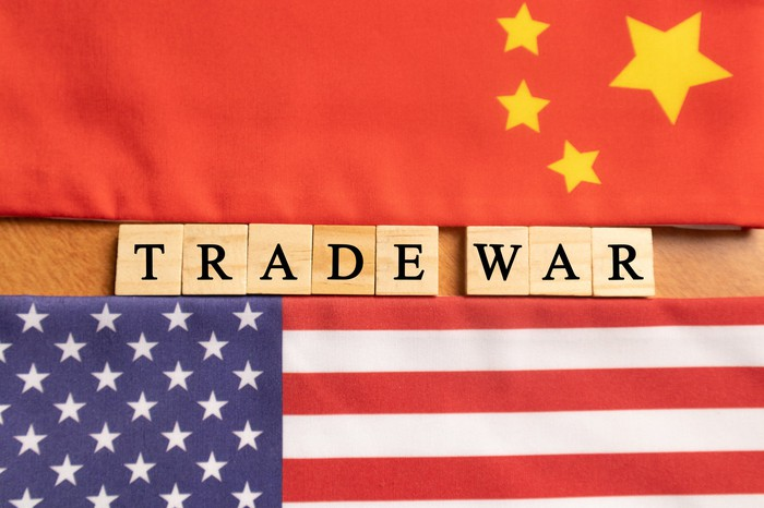 Flags of China and the US with tiles spelling out Trade War