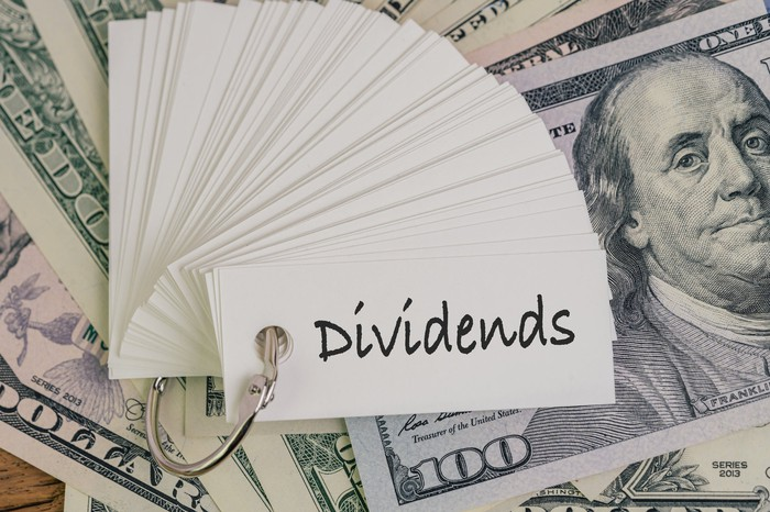 Cash with tags saying dividends on top