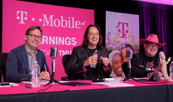 T-Mobile management seated at a table with microphones
