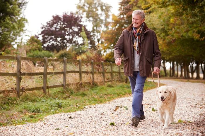 Smiling older man walking a dog