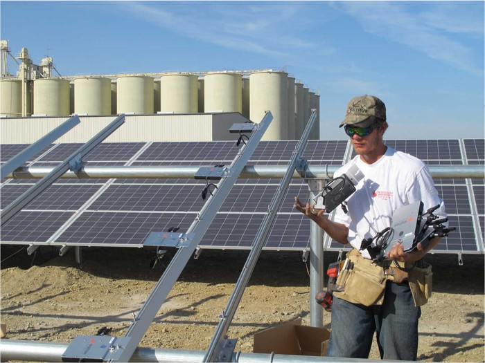Person carrying tools at a worksite with solar panels and framework.