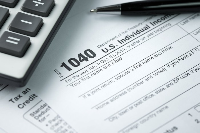 1040 tax form with calculator and pen.