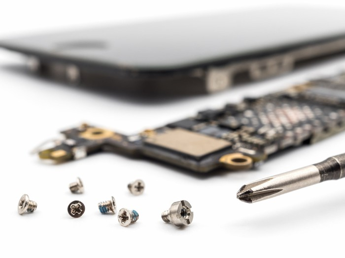 Close-up shot of a disassembled smartphone, surrounded by screws and components.