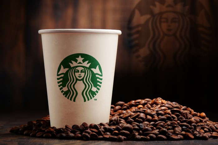 Starbucks coffee cup with coffee beans