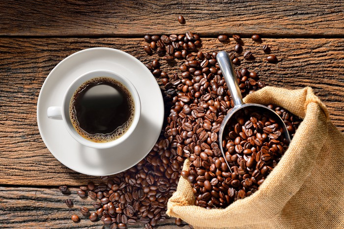 An overhead view of a cup of coffee on a wooden table, next to a scoop and a bag of coffee beans spilling out.