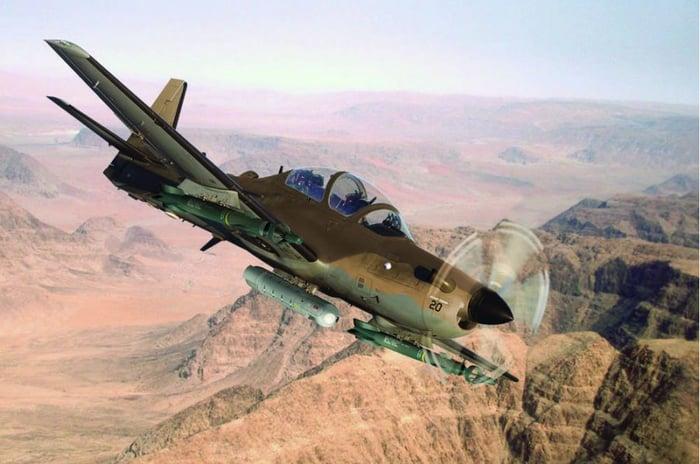 The A-29 in flight over a desert scene.