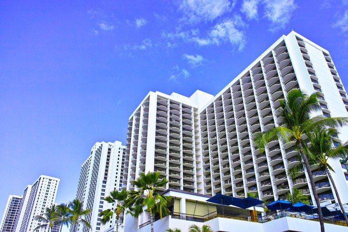 A multi-story hotel complex with white facade, flanked by palm trees.
