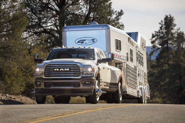 A 2019 Ram 3500 heavy-duty pickup is shown towing a horse trailer up a hill.