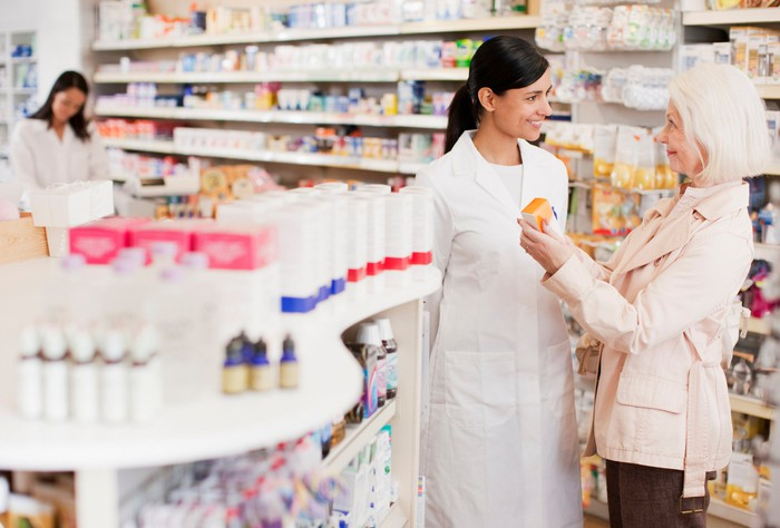 A pharmacist standing in a drugstore talking with an older customer