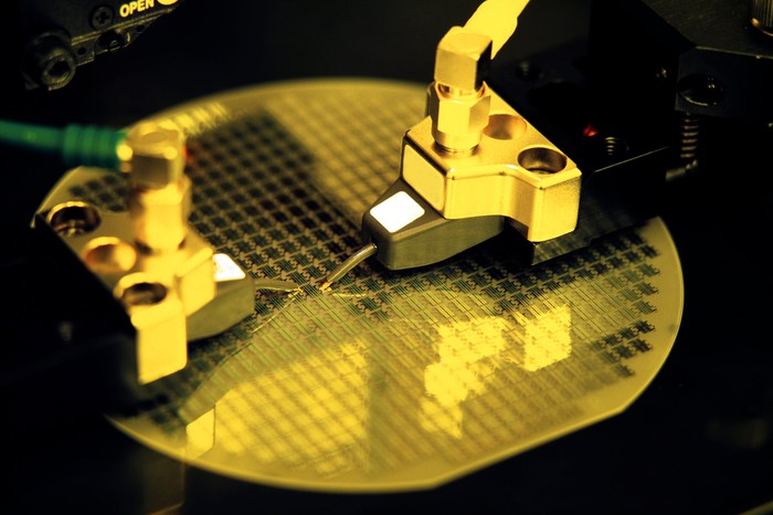 An unfinished semiconductor wafer is being procesed by several robotic tools.