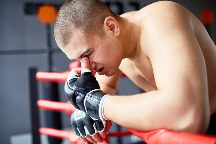 Defeated MMA fighter sits against the ropes.