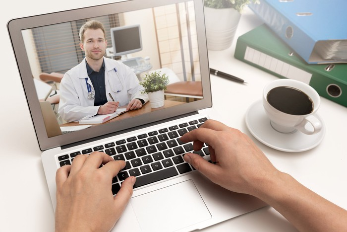 Hands on a laptop video chatting with a doctor