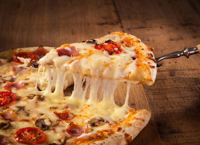 A pizza slice being served.