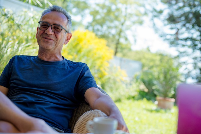 Smiling older man sitting in a chair outdoors