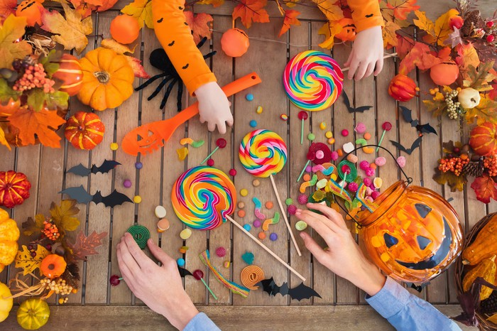 Hands grabbing Halloween candy from a table covered with Halloween decorations.