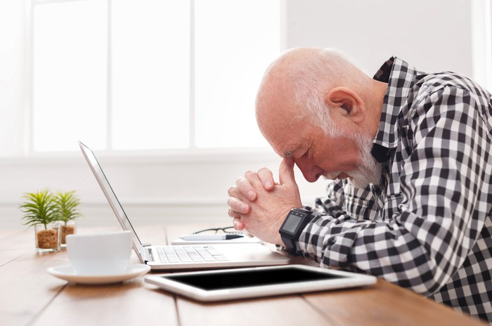 Older man sitting at a laptop bent over with clasped hands, pressing thumbs into his forehead