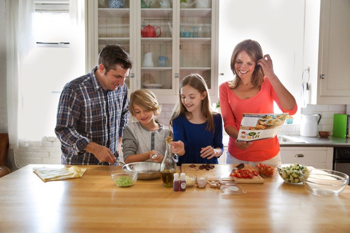 A family of four preparing a Blue Apron meal in their kitchen