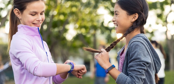 Two smiling girls with wearable devices on their wrists, in an outdoor setting.