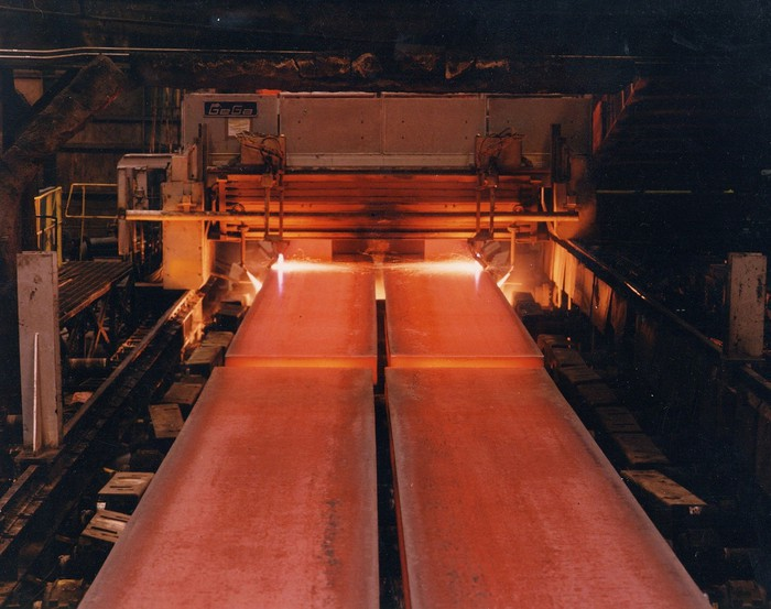 Two rows of red-glowing steel coming out of a furnace on a conveyor belt.