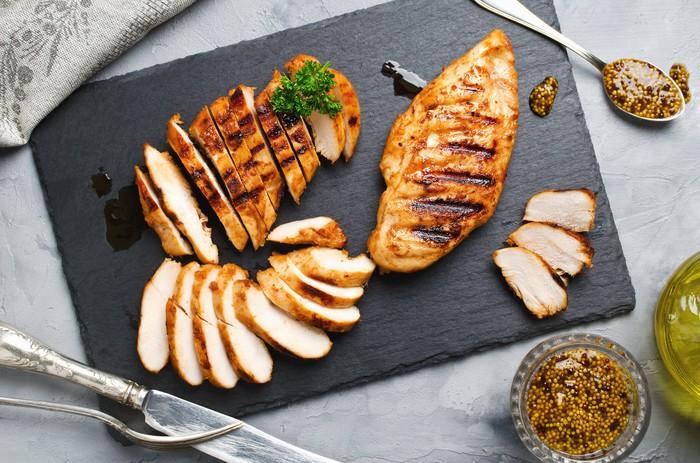 Grilled chicken on a plate surrounded by seasoning.