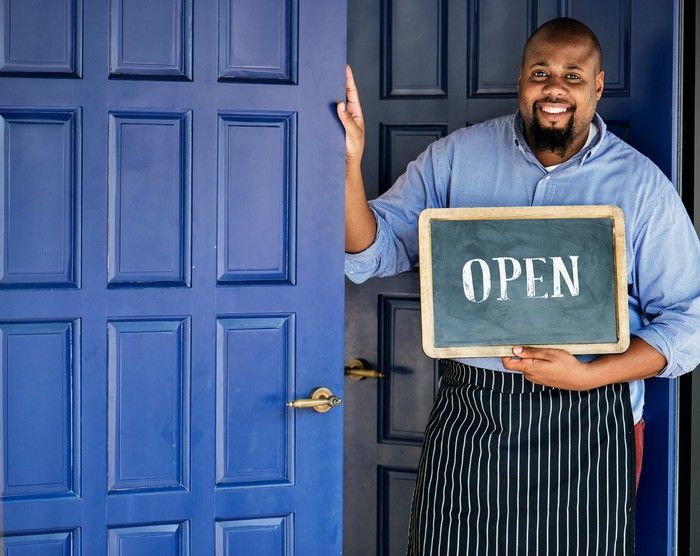 Smiling man in apron putting his hand up to a blue door and holding a small chalkboard with the word open on it