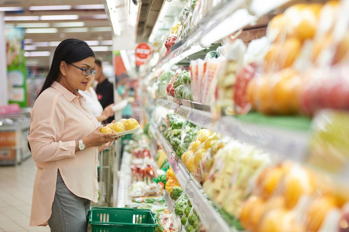 Woman at produce cooler at grocery store examining produce