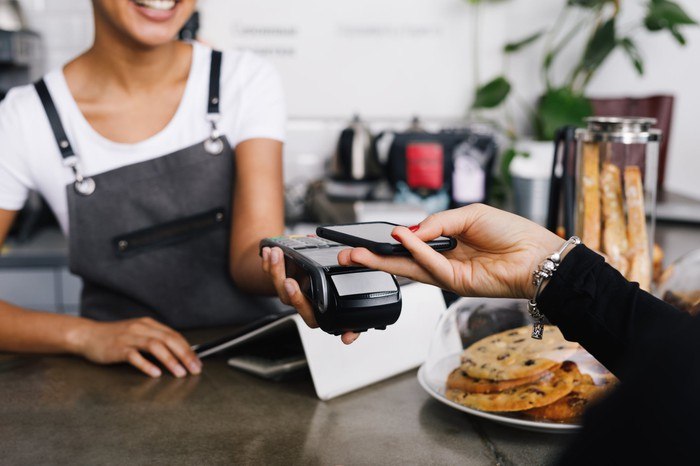 A woman's hand holding a smartphone and making a mobile payment to a server behind the counter at a coffee shop.