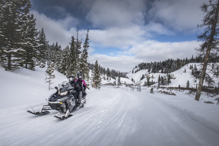 Two people on a Polaris snowmobile