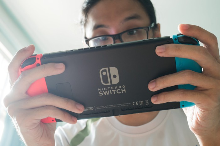 A young gamer in glasses holds his Nintendo switch viewed from below with his eyes peering over.