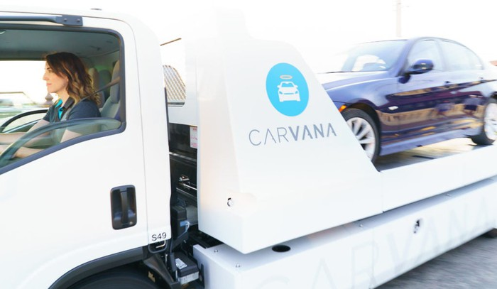 A Carvana employee drives a truck loaded with a vehicle to make a delivery to a customer.