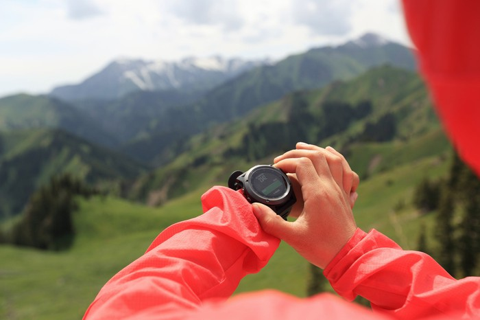 A hiker interacts with her smartwatch.