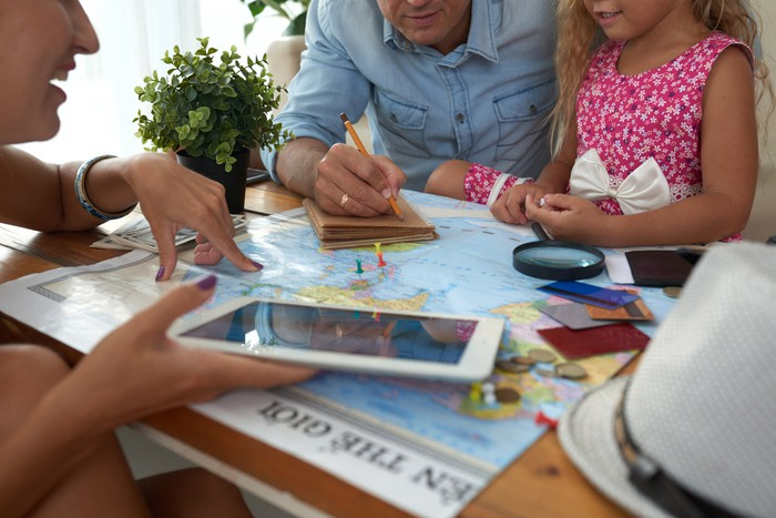 A man, a woman, and a young girl look at a map and a tablet. The man is taking notes.