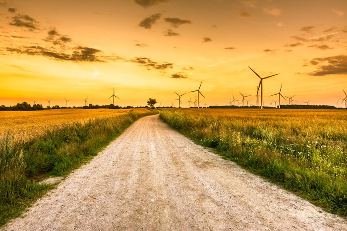 A road heading towards wind turbines in a field.