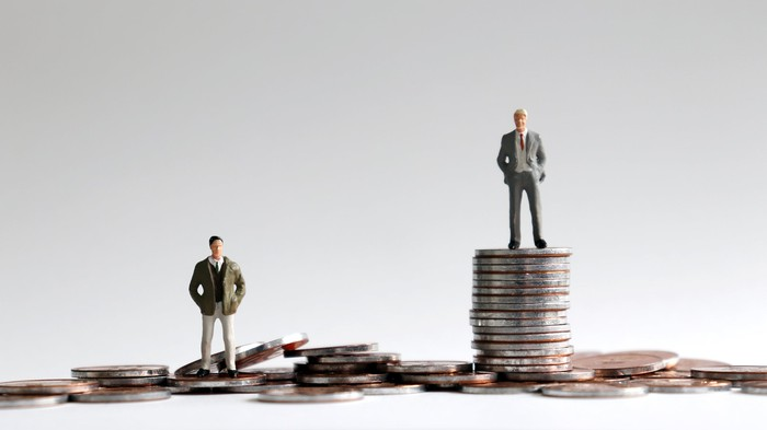 Miniature people standing on stacks of coins.