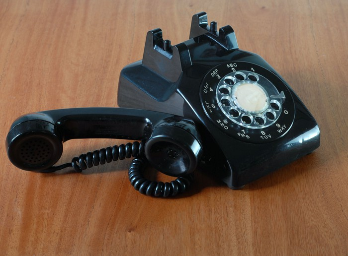Black rotary dial phone with handset off the hook
