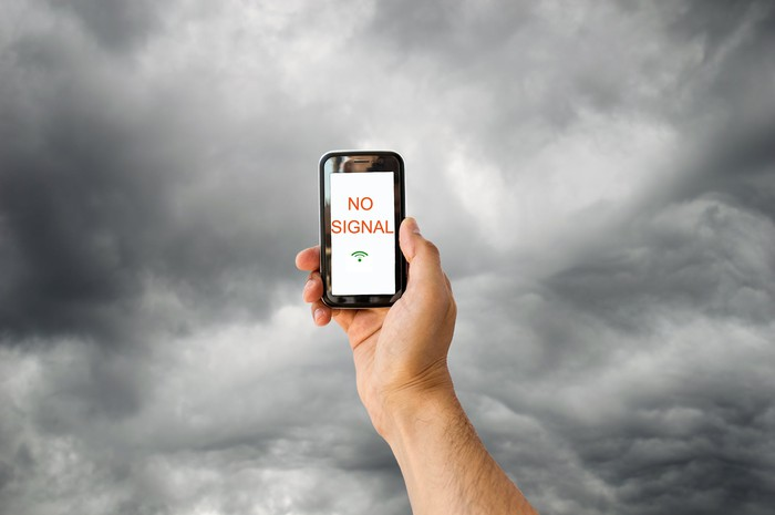 Against a sky full of storm clouds, a hand holds up a smartphone showing No Signal in red on an otherwise white screen.