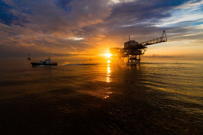 A ship sails near an offshore drilling rig at sunset.