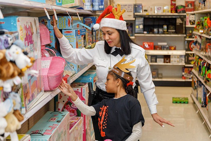 Adult female with Santa hat helping child with reindeer ears choose a toy from Target shelves.