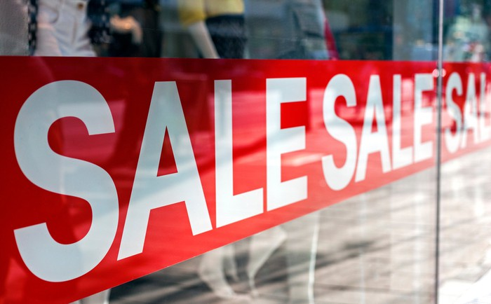 SALE sign in a shop window with white letters and a red background.