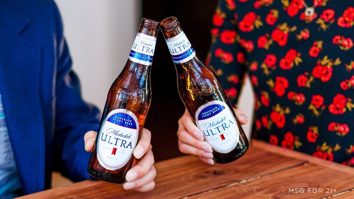 A man and woman toast bottles of Michelob Ultra.