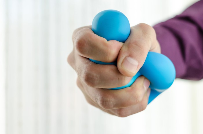A hand squeezing a stress ball hard.