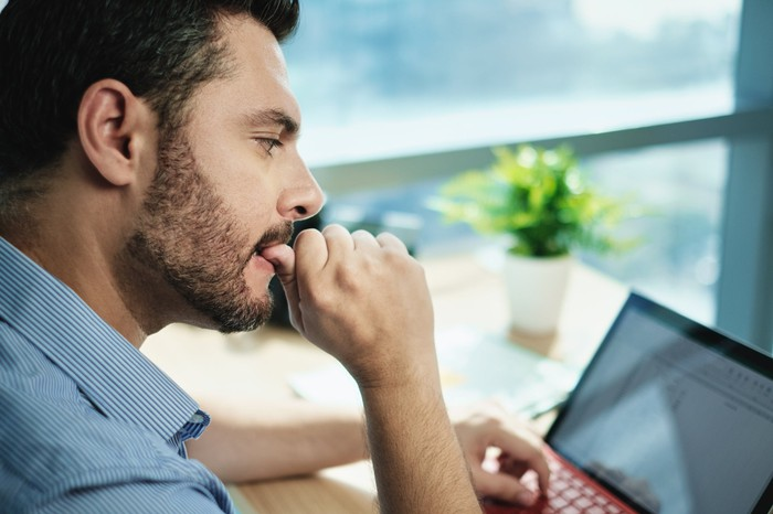 Man looking at a laptop and biting his thumb